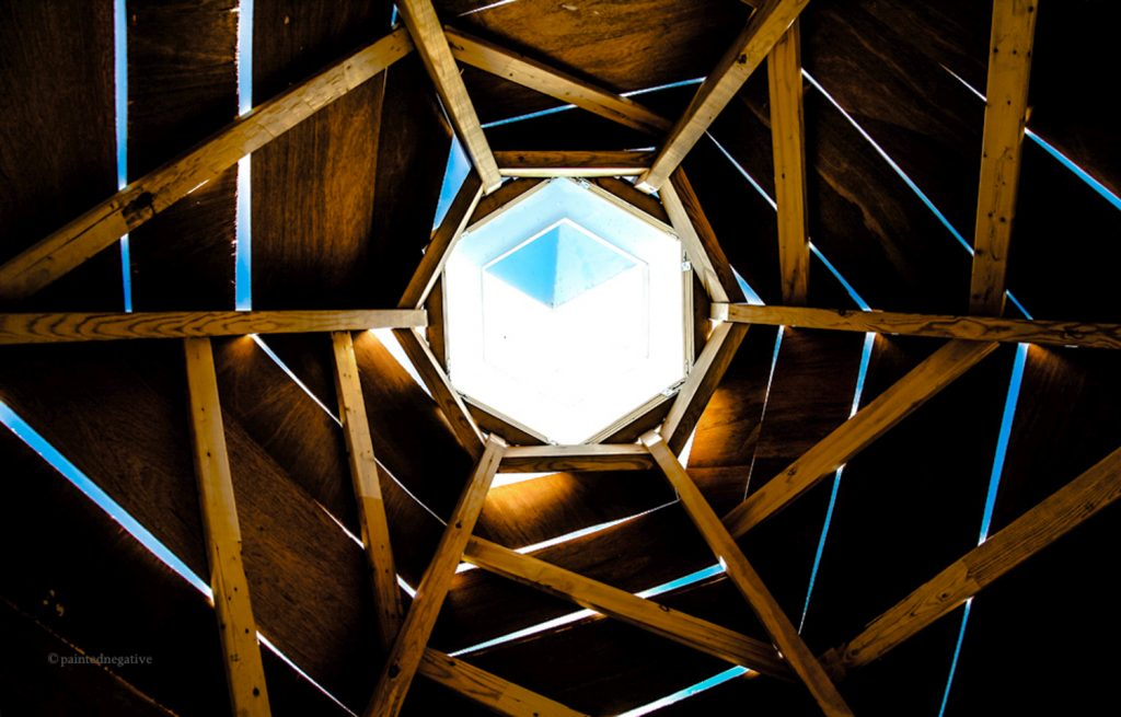 A sky-facing photo taken from the inside of a geometric art piece, sunlight shines through a hexagonal portal at image centre, surrounded by a complimentary wooden structure