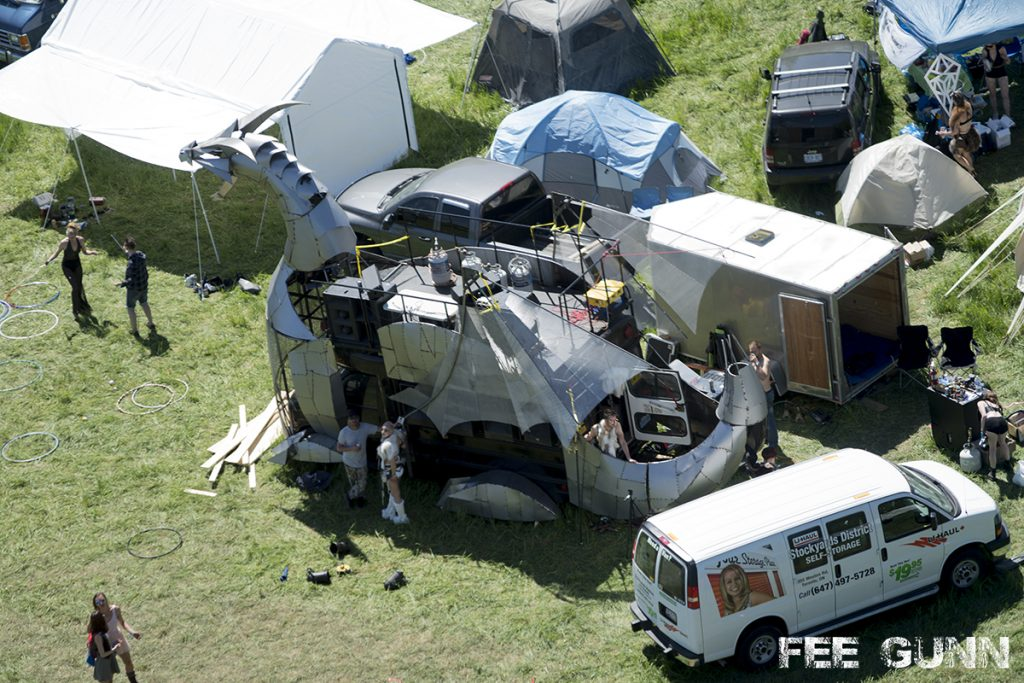 A vehicle that has been converted in to a dragon (known as Heavy Meta) sits in a grassy field during the day, surrounded by vans, trailers and tents.